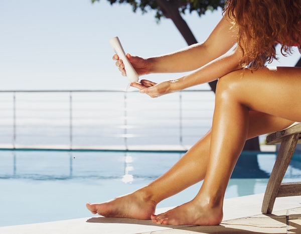 Woman sitting on deck chair by the swimming pool